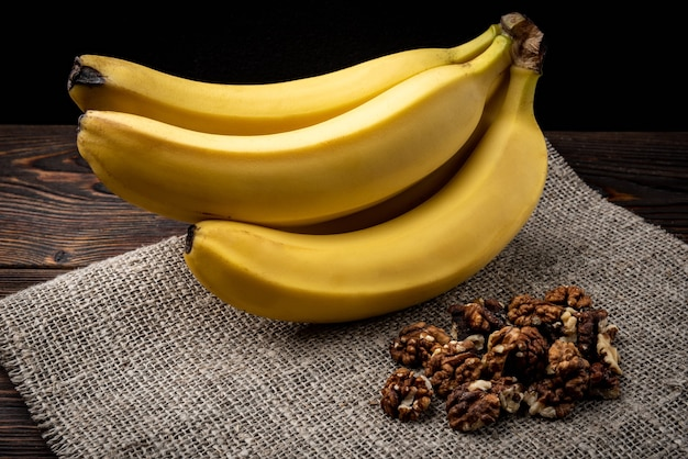 Banane und walnuss auf dunklem hölzernem hintergrund.