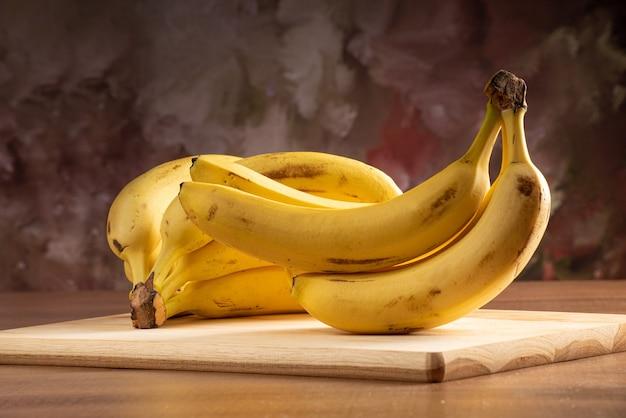 Bananen auf holz auf einem tisch, dunkler abstrakter hintergrund, gerichtetes licht, selektiver fokus.
