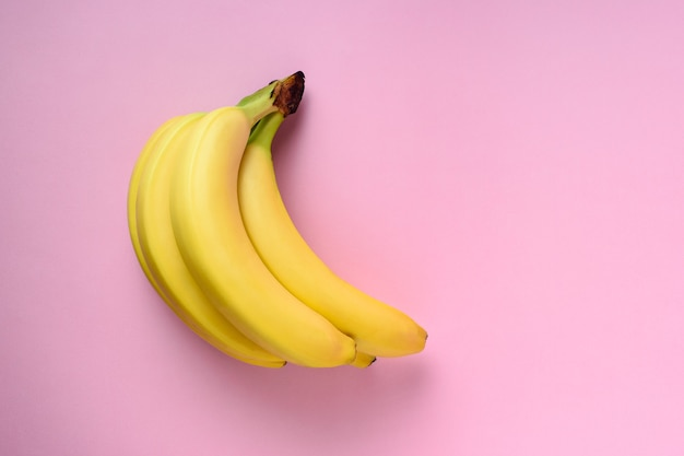 Bananen auf rosa oberfläche.