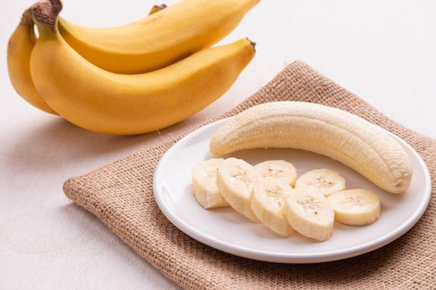 Bananen in der platte (schöne form) auf weißem holz