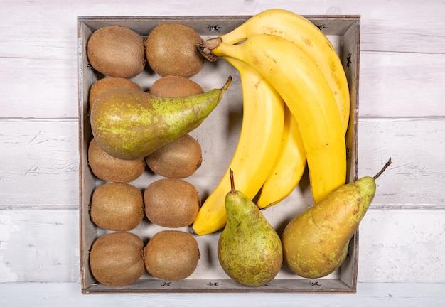 Bananen, konferenzbirnen und kiwis in einem alten holztablett auf altem holzboden.