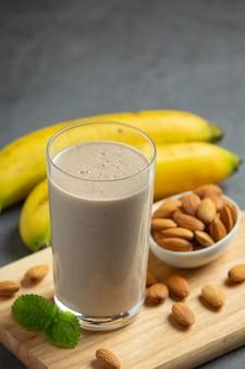 Bananen-mandel-smoothie auf dunklem hintergrund