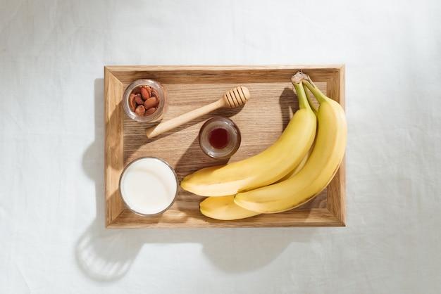 Bananen, mandeln und milch auf einem holzteller