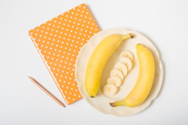 Bananen; notizbuch und bleistift auf weißem hintergrund