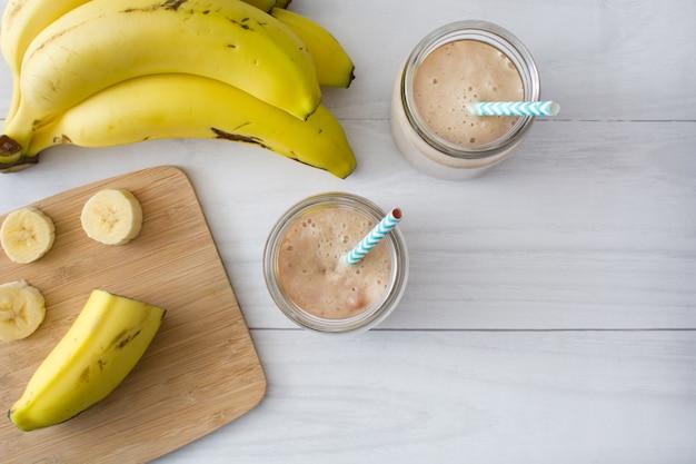 Bananen-smoothie auf einem weißen hölzernen tischkopienraum der tischplatte