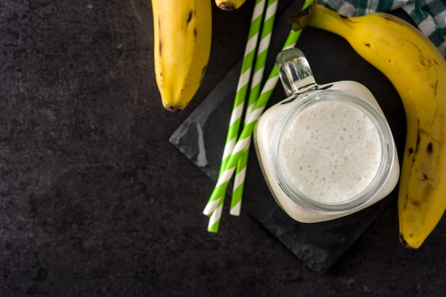 Bananen-smoothie im glas auf schwarzer draufsicht