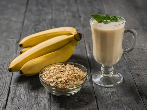 Bananen-smoothie in einem glasbecher mit haferflocken