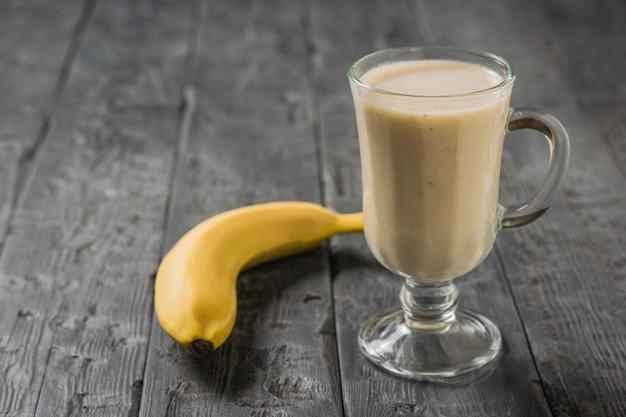 Bananen-smoothie mit haferflocken und banane auf einem holztisch