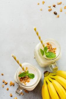 Bananen-smoothie mit müsli, getrockneten früchten und minze auf grauer betonoberfläche