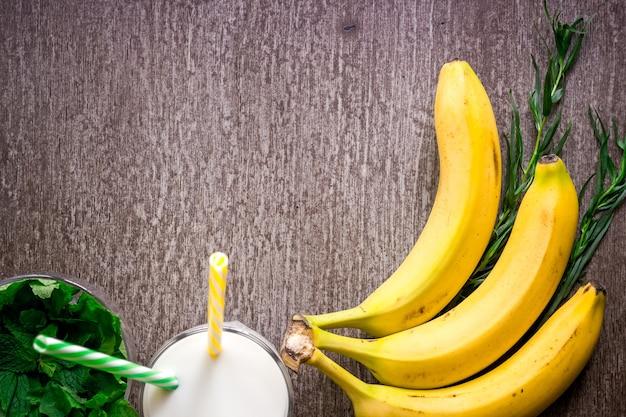 Bananen-smoothie und frische banane auf holztisch