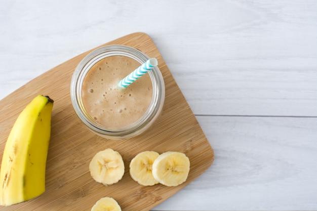 Bananen-smoothies im glas auf weißer hölzerner tischoberansicht