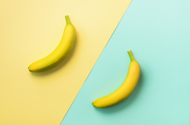 Bananen über blauem und gelbem hintergrund. buntes fruchtmuster mit kopienraum. banane in minimaler flachlage.