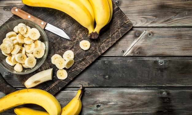 Bananen und bananenscheiben in einem teller auf einem schwarzen schneidebrett mit einem messer. auf einem hölzernen hintergrund.