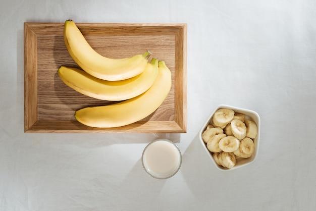 Bananen und bananenstücke auf einem holzteller