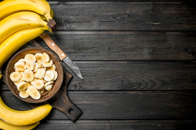 Bananen und bananenstücke in einem holzteller auf einem schneidebrett mit einem messer. auf einem schwarzen holz.