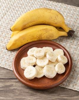 Bananen und scheiben auf einem teller über holztisch.