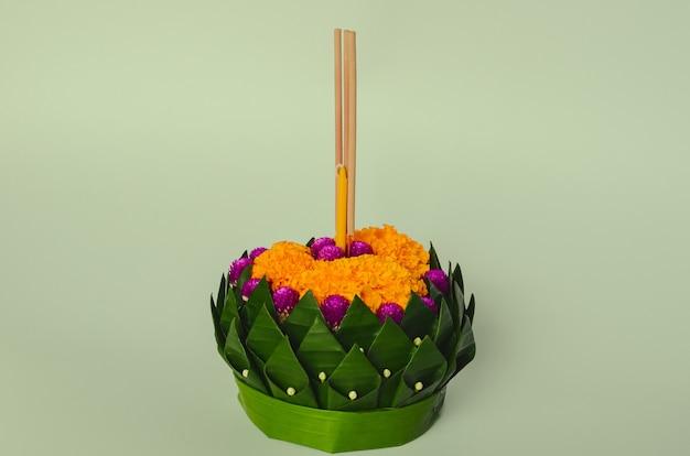 Bananenblatt krathong, die 3 räucherstäbchen und kerze haben, verziert mit blumen für thailand vollmond oder loy krathong festival auf grünem hintergrund.