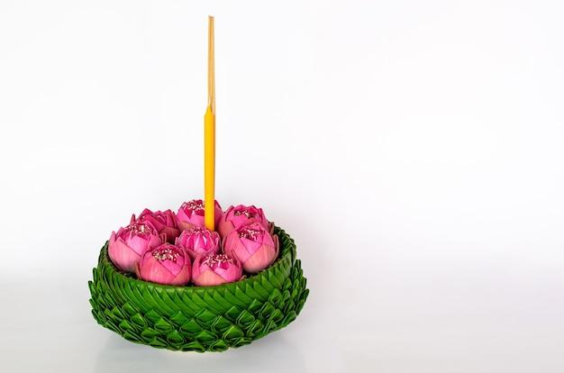 Bananenblatt-krathong, die 3 räucherstäbchen und kerze haben, verziert mit rosa lotusblumen für thailand-vollmond oder loy krathong-festival einzeln auf weißem hintergrund.