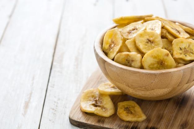 Bananenchips in der schüssel auf weißem holztisch