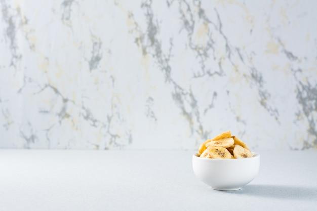 Bananenchips in einer weißen schüssel auf dem tisch. fast food. speicherplatz kopieren