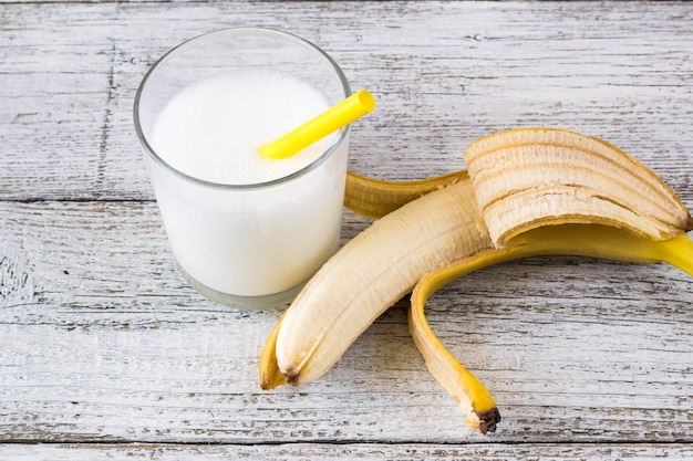 Bananencocktail und frische bananen auf hölzernem