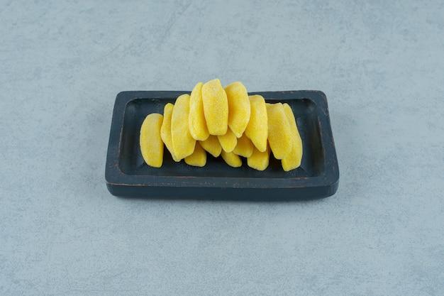 Bananenförmige kaubonbons in einem holzbrett auf weißer oberfläche