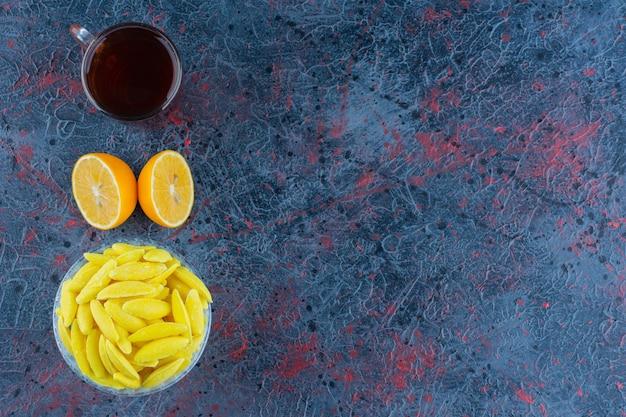 Bananenförmige kaubonbons mit einer tasse schwarzen tee und gehackter zitrone.
