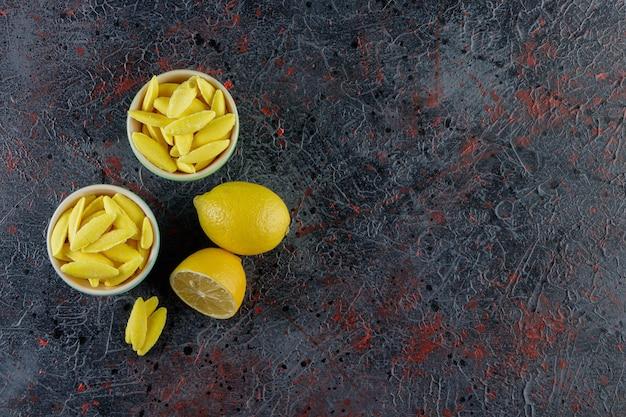 Bananenförmige kaubonbons mit frischer zitrone auf einer dunklen