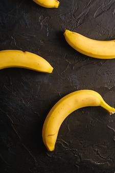 Bananenfrüchte auf dunklem strukturiertem hintergrund, draufsicht