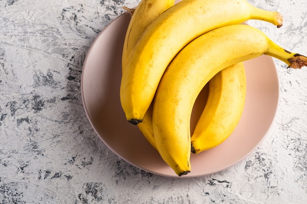 Bananenfrüchte in der rosa platte auf weißem strukturiertem hintergrund, kopierraum der draufsicht