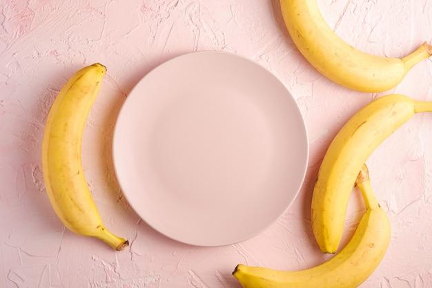Bananenfrüchte mit leerem rosa teller auf rosa strukturiertem hintergrund, kopierraum der draufsicht