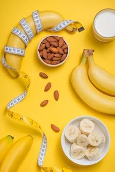 Bananenglas milch und mandeln mit maßband auf gelbem hintergrund mit kopierraum