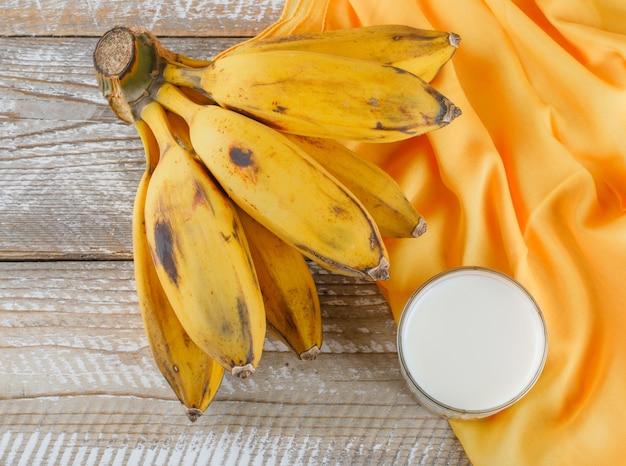 Bananenhaufen mit milch auf holz und textil,
