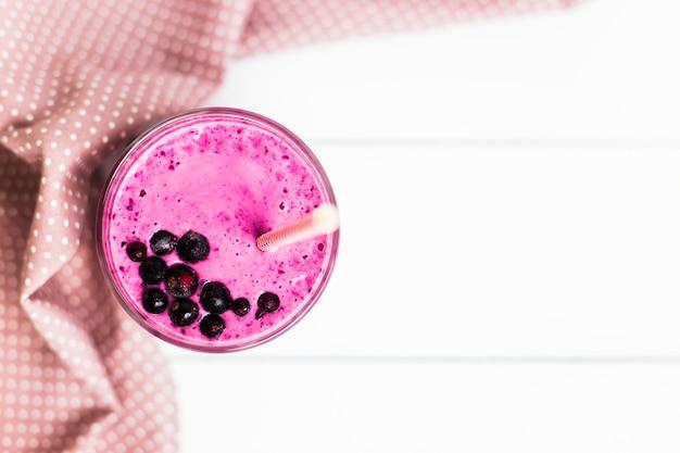 Bananenkorinthe smoothies in einem glas auf einer weißen tabelle nahe bei einer rosa serviette in den tupfen mit einem strohhalm