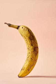 Bananenkreatives poster mit dunklen punkten, überreife früchte auf rosafarbenem hintergrund im flug. essen mit bedacht konsumieren