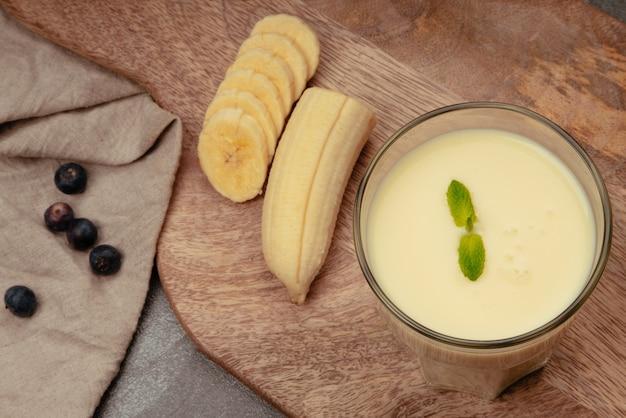 Bananenmilchshake mit minze auf holzschneidebrett und leinengeschirrtuch