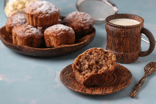 Bananenmuffins mit haferflockenflocken, bestreut mit puderzucker auf einem kokosnussteller und einer tasse milch