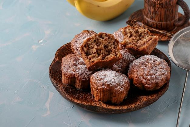 Bananenmuffins mit haferflockenflocken mit puderzucker auf einem kokosnussteller bestreut