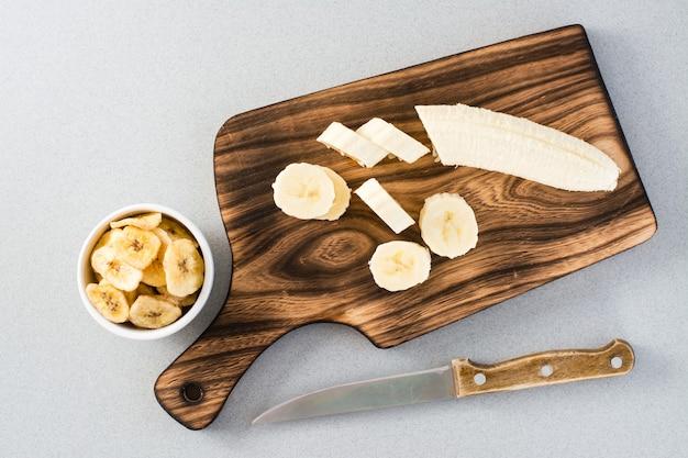Bananenscheiben auf einem schneidebrett und ein messer und bananenchips in einer schüssel auf dem tisch