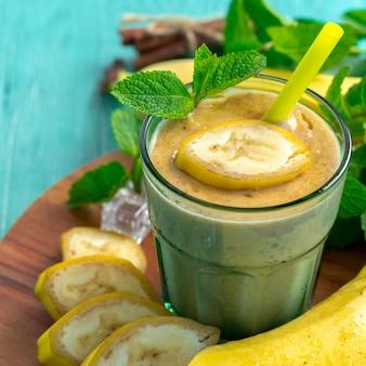 Bananensmoothie und frische banane auf holztisch.