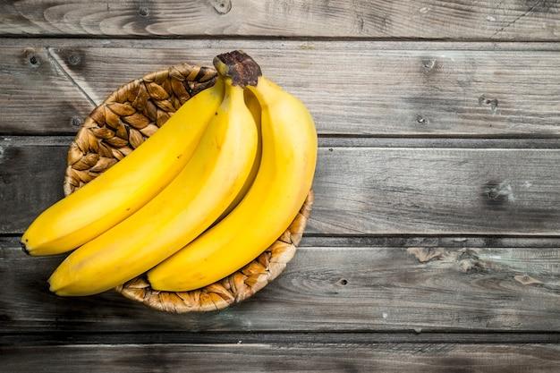 Bananenstaude im korb. auf einem schwarzen hölzernen hintergrund.