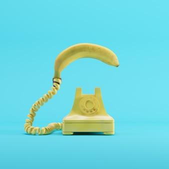 Bananentelefon mit gelbem weinlesetelefon auf blauem pastellfarbhintergrund. minimales ideenkonzept.