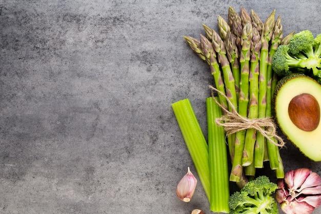 Banches von frischem grünem spargel und gemüse auf holztisch, draufsicht