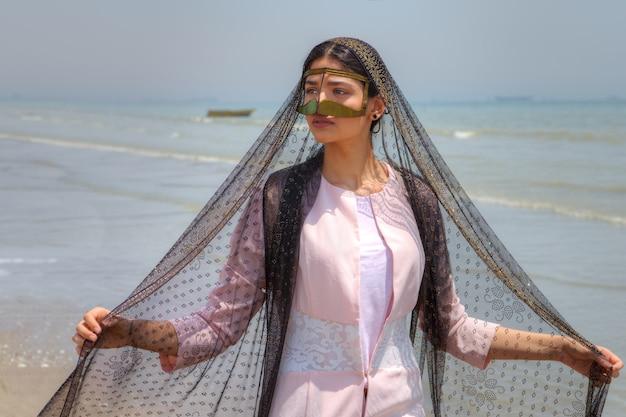 Bandari frau trägt traditionelle maske, strand des persischen golfs, hormozgan, iran.