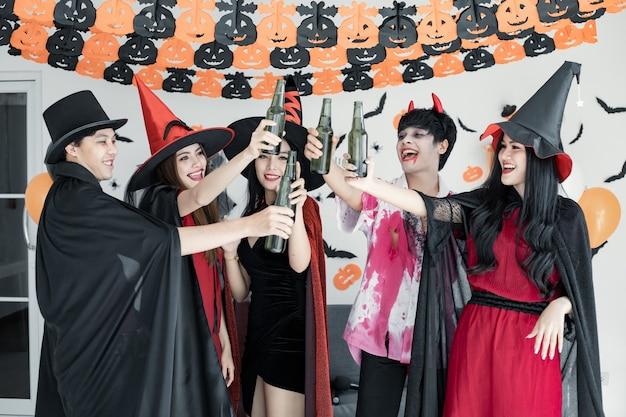 Bande junger asiaten in kostümhexe, zauberer mit feiern halloween-party für tanz und getränk und betrunken im raum. gruppe teen thai mit halloween feiern. konzeptparty halloween zu hause.