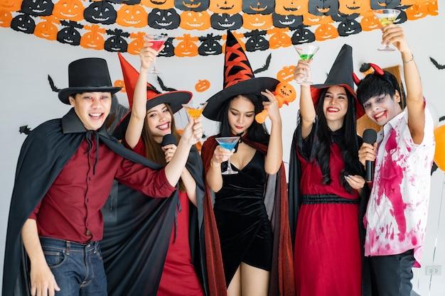Bande junger asiaten in kostümhexe, zauberer mit halloween-party zum singen eines liedes und trinkens, dessert im zimmer. gruppe jugendlich thai mit halloween feiern. konzeptparty halloween zu hause.