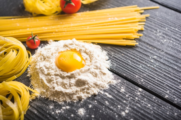 Bandnudeln und spaghettis mit eigelb auf mehl über dem holztisch