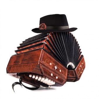 Bandoneon, tangoinstrument mit einem männlichen hut auf die oberseite auf weiß