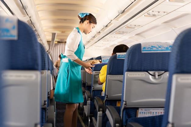 Bangkok airways flugbegleiter servieren den passagieren an bord speisen.