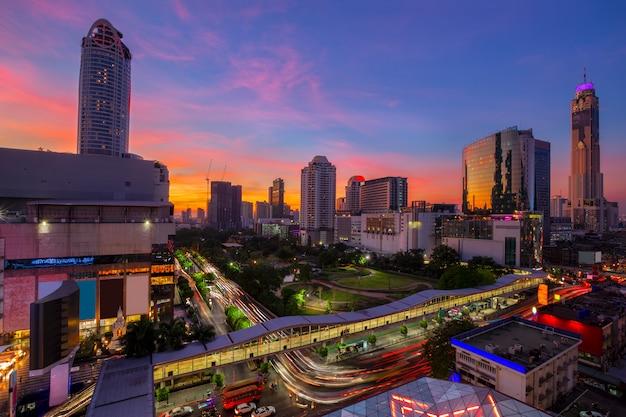 Bangkok-geschäftsgebiet mit dem öffentlichen parkbereich im vordergrund zur sonnenuntergangzeit